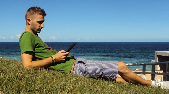Lubo Jurík číta Amazon Kindle na pláži v Austrálií